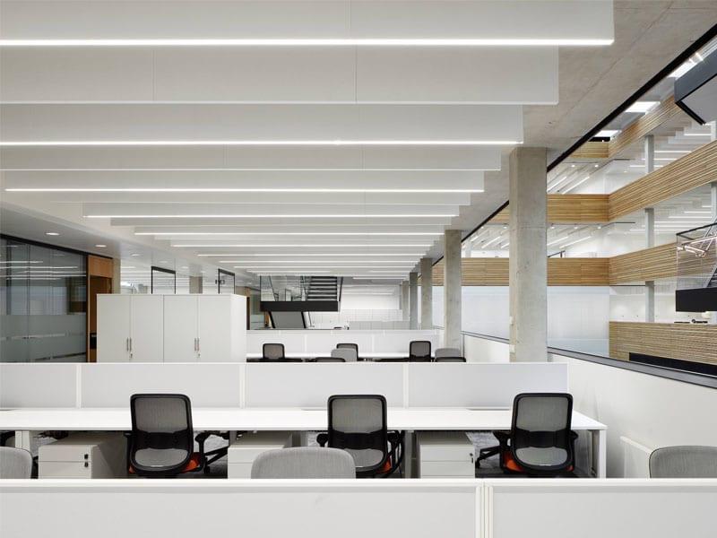 Blade indbygget i akustik bafler nedhængt fra loft i åbent kontormiljø - Luminex