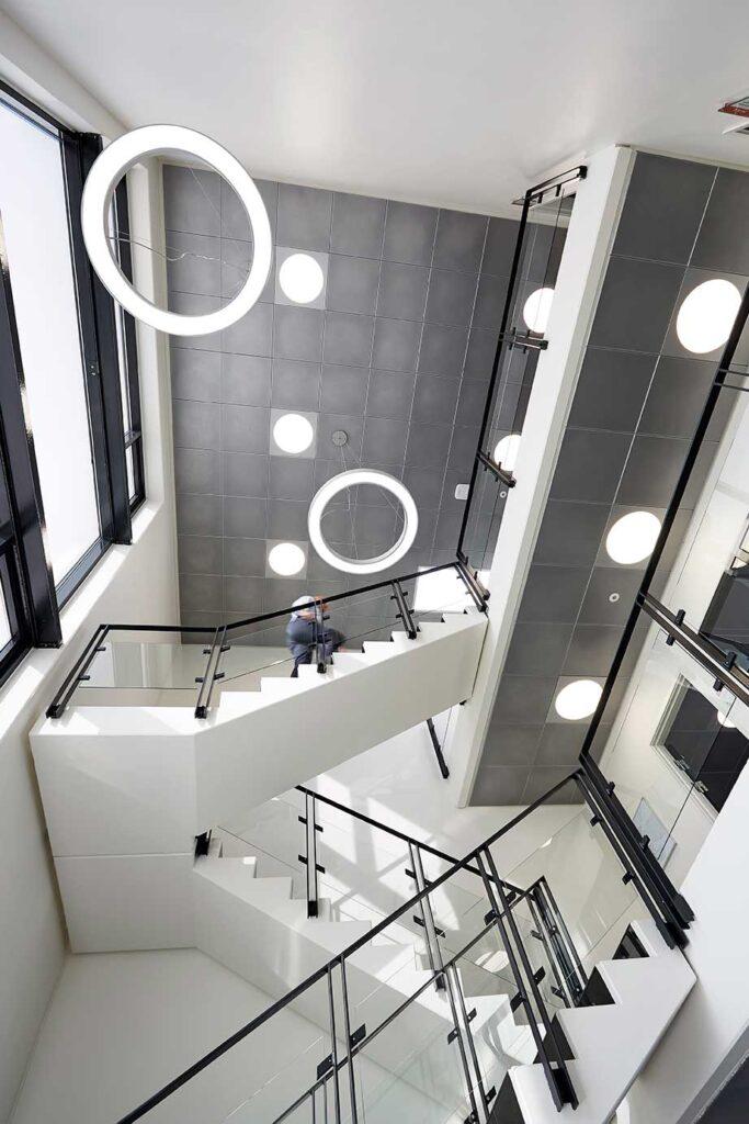 Ledgo Circle panel indbygget i loft med Ringo Star cirkulær lampe nedhængt fra loft ved trapperne - Luminex