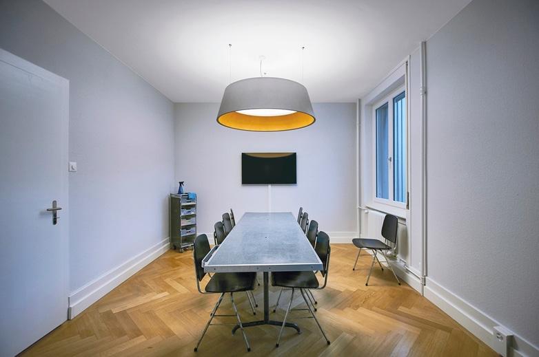 Beam me up lampe med skærm i beton look nedhængt over mødebord - Luminex