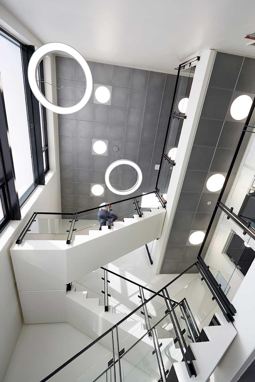 Cirkulært panel lampe indbygget i loft med Ringo star rund lampe nedhængt fra loft i trappe opgang - Luminex