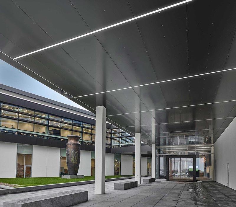 Matric monteret som kontinuerligt lysbånd udendørs under udhæng ved indgang til bygning - Luminex