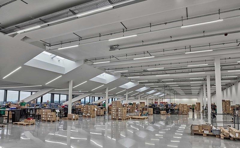 Linia LED indsats lampe monteret i skinnesystem nedhængt fra loft i lagerhal - Luminex