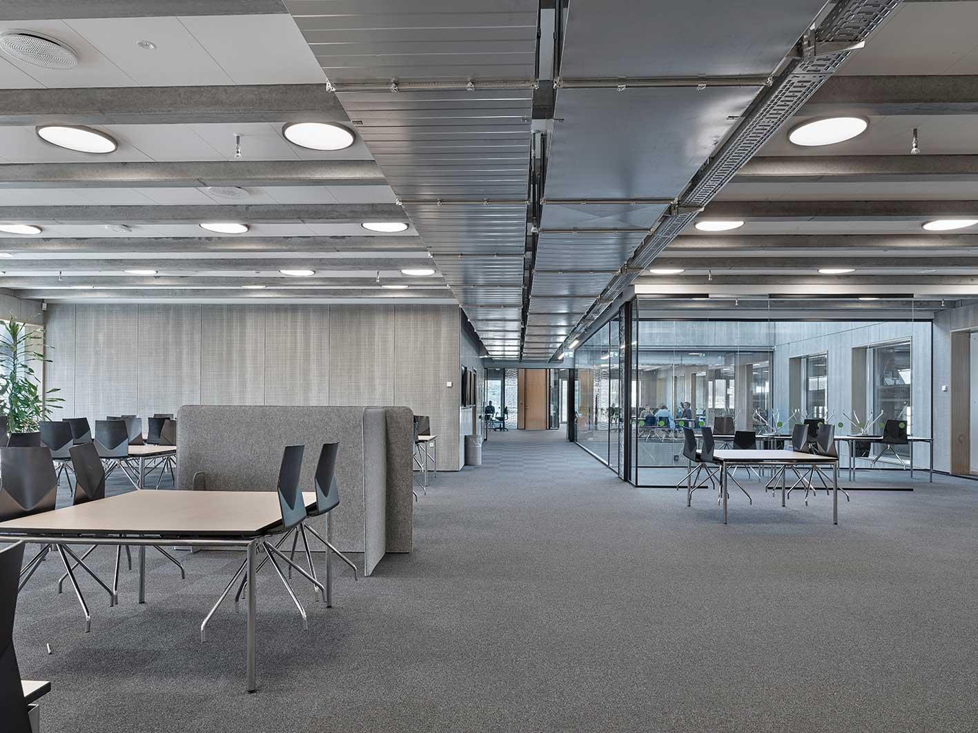 Basic rund flad lampe monteret i rækker direkte på loft i læsesal hos VUC - Luminex