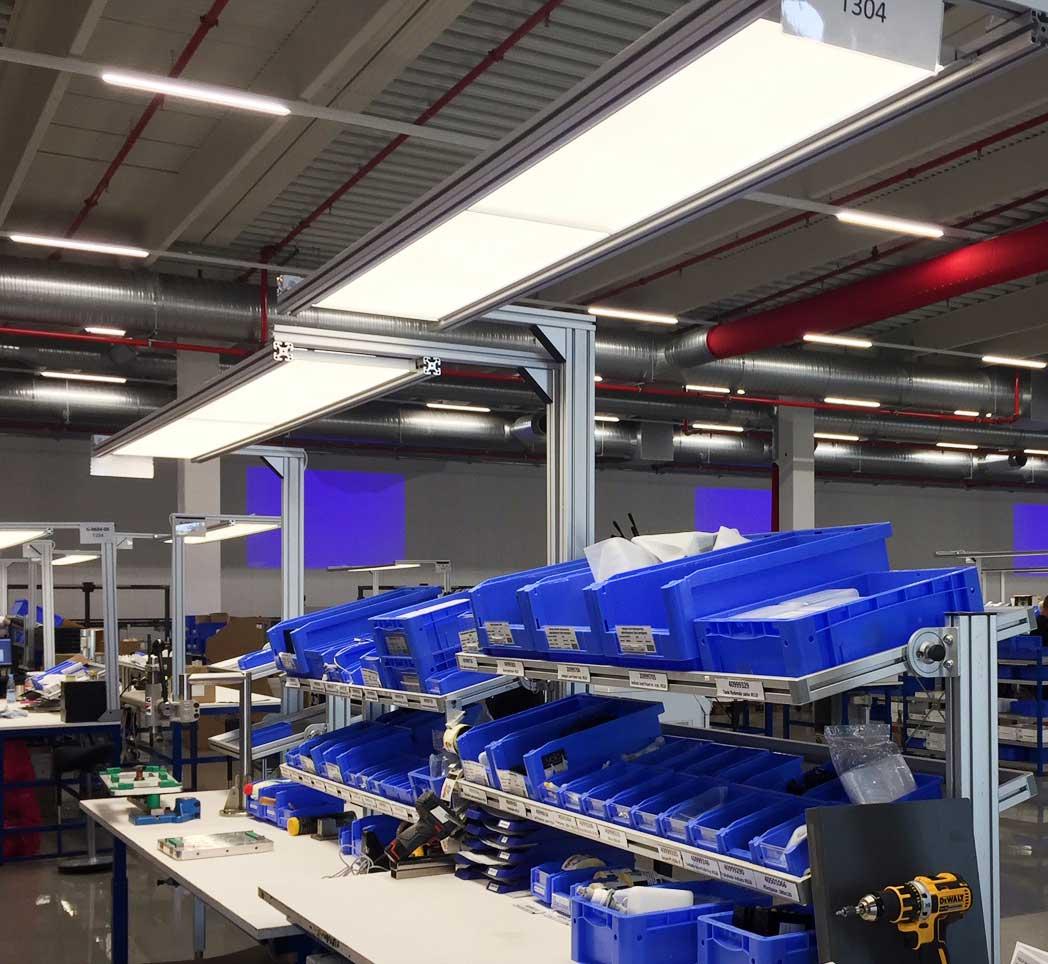Caleo flad lampe monteret i skinner ved arbejdsstationer som fokuslys Linia monteret i skinnesystem som grundbelysning i arbejdshal - Luminex
